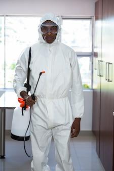 Portret van de ongediertebestrijdingsmens die zich met insecticidespuitbus bevinden
