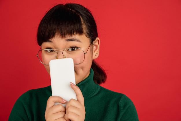 Portret van de oost-aziatische jonge mooie vrouw op rode achtergrond met copyspace.