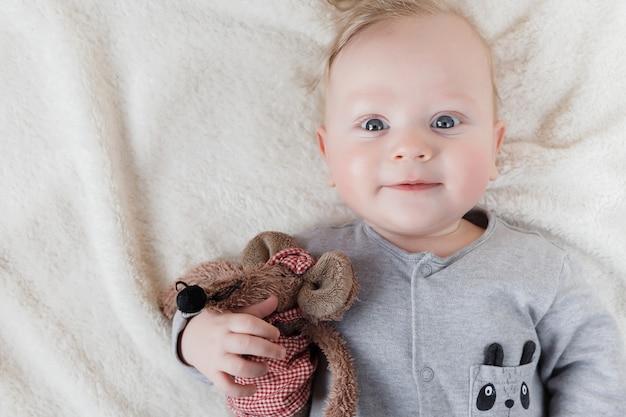 Portret van de oude babyjongen van vijf maanden met zacht stuk speelgoed op witte deken Premium Foto