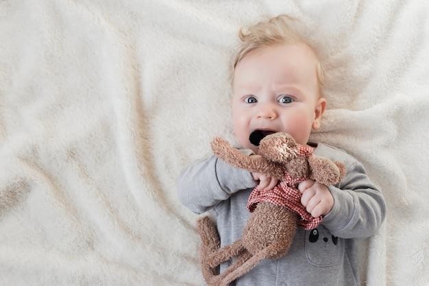 Portret van de oude babyjongen van vijf maanden met zacht stuk speelgoed op witte deken