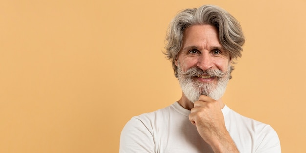 Portret van de oude mens die met exemplaar-ruimte glimlacht