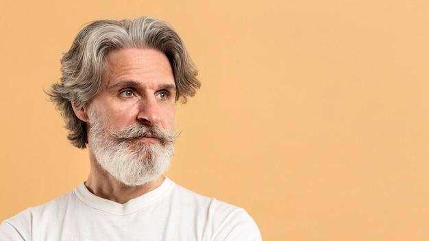 Portret van de oude mens die weg met exemplaar-ruimte kijkt