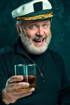 Portret van de oude zeemansmens als kapitein in zwarte sweater en hoed die cognac op zwarte studio drinken