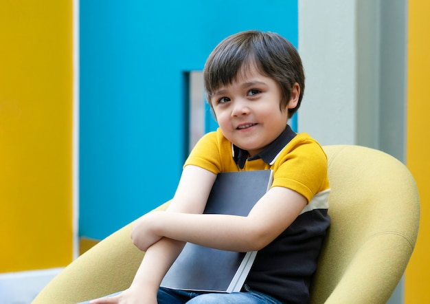 Portret van de positieve zitting van de kindjongen op gele stoel die zijn favoriet boek, een gelukkig schooljong geitje met smiliggezicht houden die met leestijd genieten van in het klaslokaal. onderwijs concept
