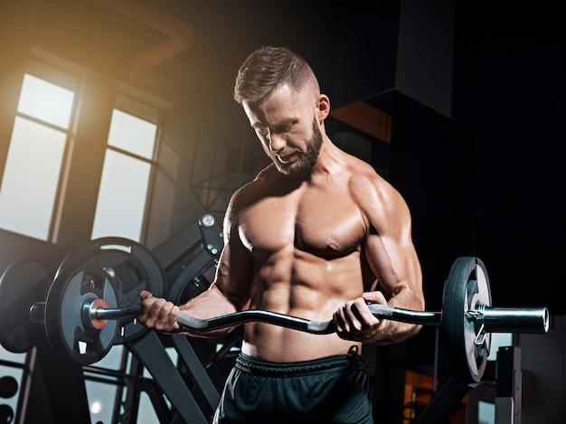 Portret van de super geschikte spier jonge mens die in gymnastiek met barbell uitwerken