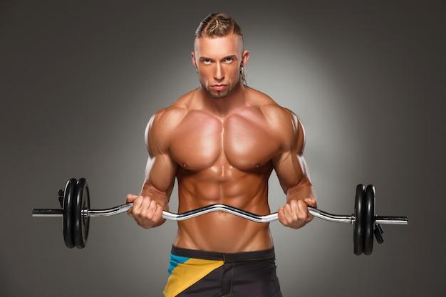 Portret van de super geschikte spier jonge mens die in gymnastiek uitwerken.