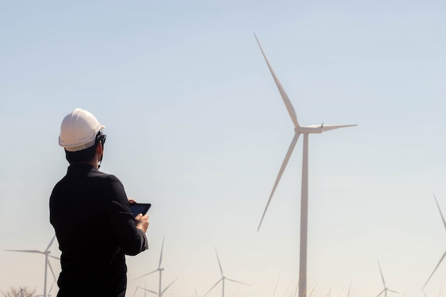 Portret van de tablet van de bedrijfs aziatische mensholding met de windturbine op achtergrond.