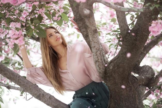 Portret van de tedere vrouw tegen de sakurabloem