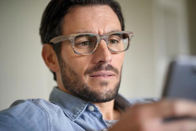 Portret van de toevallige knappe mens die cellphone controleert en ontwerperglazen draagt