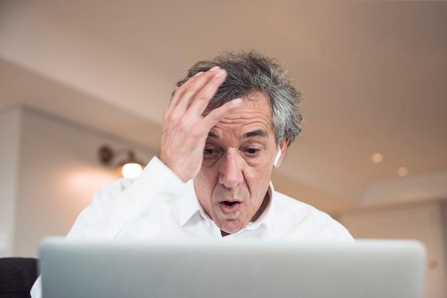 Portret van de verraste hogere mens die laptop bekijkt