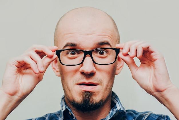 Portret van de verraste jonge knappe mens die glazen draagt