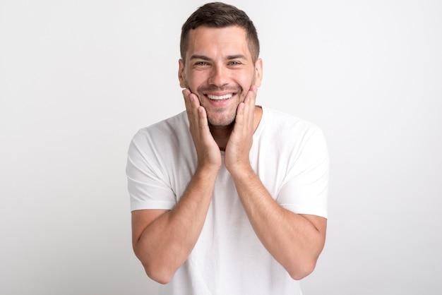 Portret van de verraste mens in witte t-shirt die zich tegen duidelijke achtergrond bevindt
