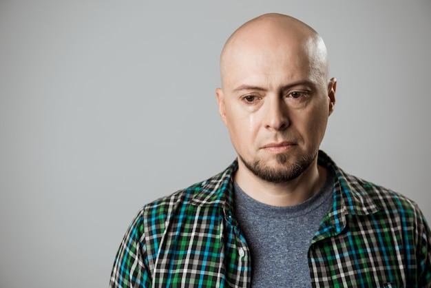Portret van de verstoorde knappe mens die over beige muur denkt