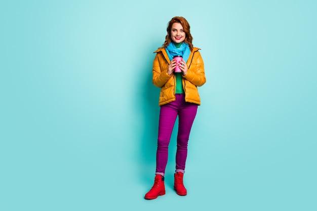 Portret van de volledige lengte van de mooie dame van de reiziger houdt warme koffie drank lopen op straat dragen casual gele overjas sjaal paarse broek coltrui schoenen.
