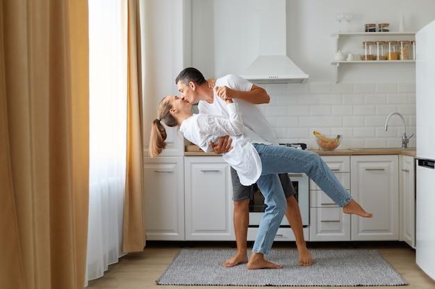 Portret van de volledige lengte van een gelukkig paar met casual kleding die samen danst in de keuken, een man die zijn vrouw kust, die graag tijd samen thuis doorbrengt.