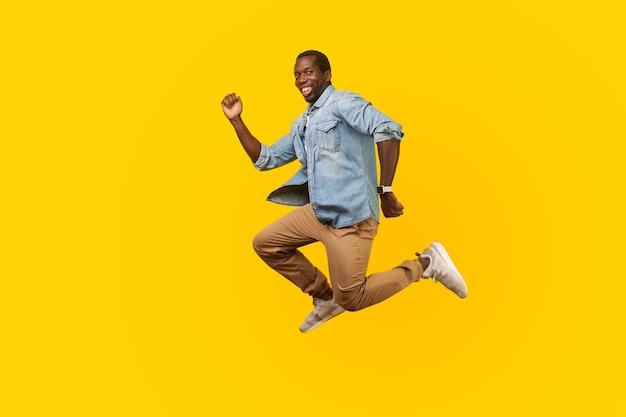 Portret van de volledige lengte van een gelukkige vrolijke man in een denim casual shirt dat springt of vliegt, haast je naar zijn droom, kijkend naar de camera met een brede glimlach. indoor studio-opname geïsoleerd op gele achtergrond