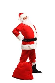 Portret van de volledige lengte van een kerstman poseren in de buurt van een zak vol geschenken geïsoleerd op een wit oppervlak
