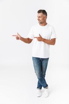 Portret van de volledige lengte van een knappe casual man die geïsoleerd op wit staat, kopieerruimte presenteert, wijst