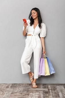 Portret van de volledige lengte van een mooie jonge brunette vrouw met een zomeroutfit die geïsoleerd staat over een grijze muur, boodschappentassen draagt, mobiele telefoon gebruikt