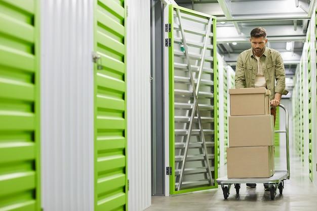 Portret van de volledige lengte van knappe bebaarde man laden kar met kartonnen dozen in self storage unit, kopie ruimte