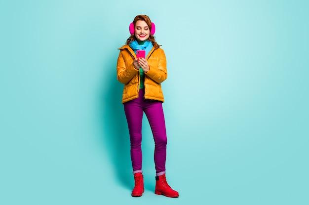 Portret van de volledige lengte van mooie reiziger dame houden telefoon zoeken kaart navigatie dragen trendy casual gele overjas sjaal paarse broek schoenen.