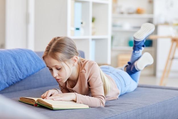 Portret van de volledige lengte van schattig blond meisje boek lezen of studeren terwijl liggend op de bank in gezellig interieur, kopie ruimte