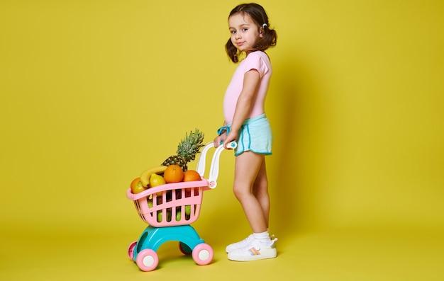 Portret van de volledige lengte van schattig meisje in roze romper en blauwe korte broek met winkelwagentje vol fruit poseren tegen gele muur. kopieer ruimte