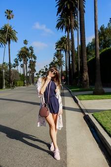 Portret van de volledige lengte van stijlvolle lachende vrouw lopen op exotische straat in de buurt van het hotel in zonnige warme dag. haar vakantie doorbrengen in los angeles