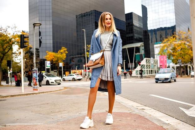 Portret van de volledige lengte van stijlvolle vrij vrolijke blonde vrouw die zich voordeed op straat in de buurt van de gebouwen van het zakencentrum, jurk jas en sneakers, mode levensstijl, positieve stemming dragen.