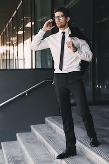 Portret van de volledige lengte van stijlvolle zakenman gekleed in formeel pak staande buiten glazen gebouw met jasje over zijn schouder, en praten over de mobiele telefoon