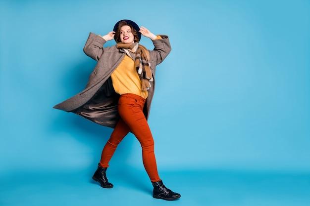 Portret van de volledige lengte van vrij trendy reiziger dame lopen straat in het buitenland goed humeur wind waait wind dragen casual lange grijze jas sjaal broek pet schoenen.