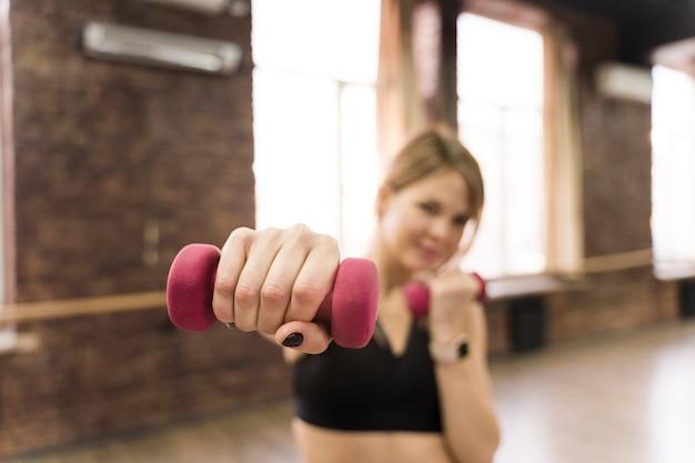 Portret van de volwassen gewichten van de vrouwenholding bij de gymnastiek