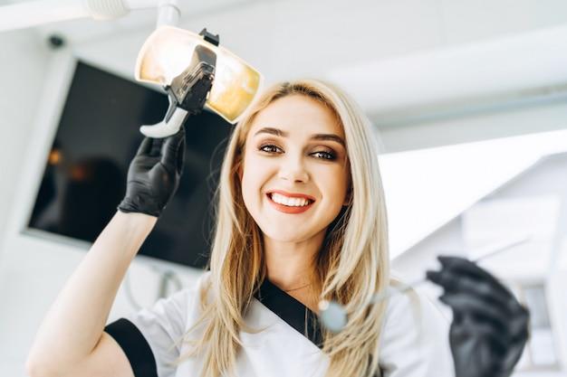 Portret van de vrij jonge vrouwelijke tandarts in een tandkliniek.