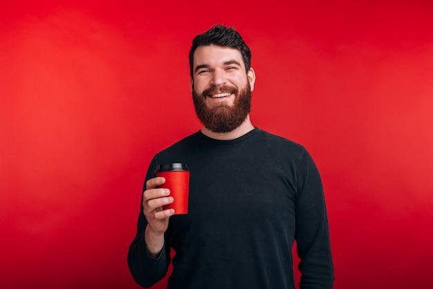 Portret van de vrolijke jonge mens met de kop van de baardholding van koffie en het bekijken zeker de camera