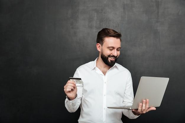 Portret van de vrolijke mens die online betaling in internet doen die notitieboekje en creditcard gebruiken, dat over donkergrijs wordt geïsoleerd