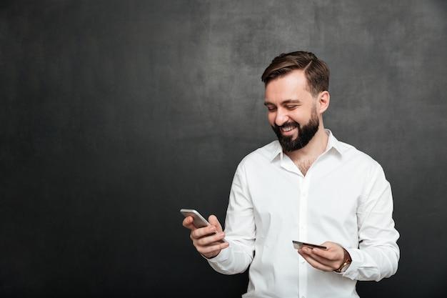 Portret van de vrolijke mens die online betaling in internet verricht die mobiele telefoon en creditcard gebruikt, die over donkergrijs wordt geïsoleerd