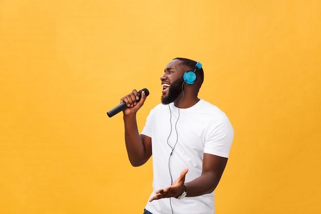 Portret van de vrolijke positieve elegante knappe afrikaanse microfoon van de mensenholding en het hebben van hoofdtelefoons