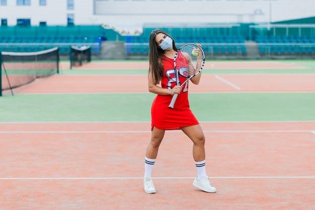 Portret van de vrouw die van de tennisspeler een bal buiten met beschermende maskers houden