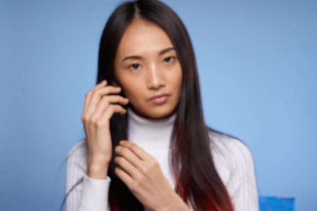 Portret van de vrouw het aziatische uiterlijk op blauw wit sweatermodel als achtergrond