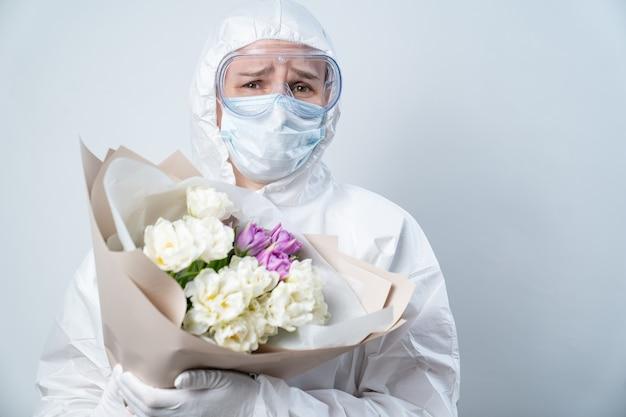 Portret van de vrouw van de dokter in beschermend pak, masker, bril en handschoenen met boeket bloemen.