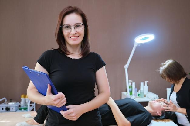 Portret van de vrouw van de eigenaar van de schoonheidssalon, die een volwassen zelfverzekerde glimlachende vrouw poseert, een achtergrondmassageprocedure op tafel