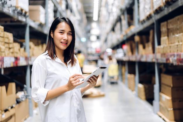 Portret van de vrouw van de managerarbeider status en orde details op tabletcomputer voor leveringen die camera op planken met goederenachtergrond in magazijn bekijken