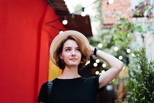 Portret van de vrouw van yong met korte kapsels in hoed in straat