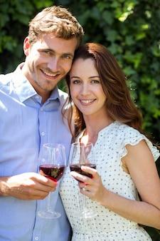 Portret van de wijnglazen van de paarholding bij voortuin