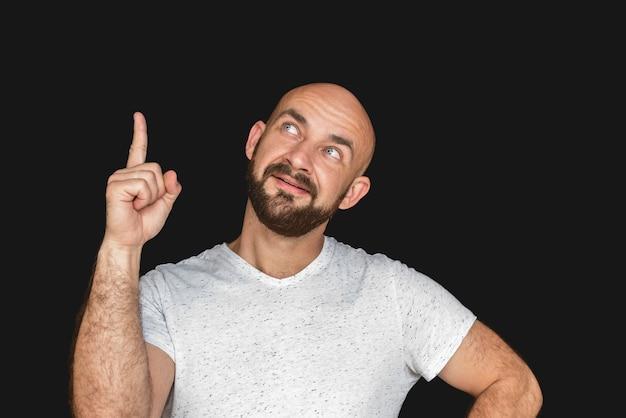 Portret van de witte kale mens met baard in witte t-shirt die en duim glimlacht toont