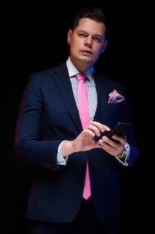 Portret van de zekere knappe ernstige elegante telefoon van de zakenmanholding in zijn handen
