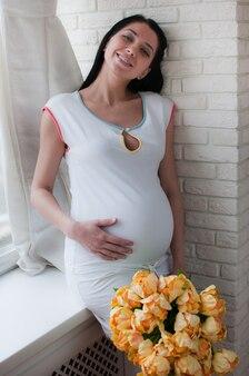 Portret van de zwangere vrouw met gele bloemen