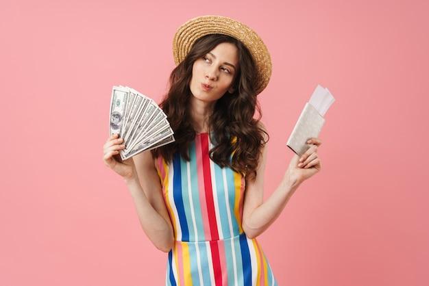 Portret van denkende dromende jonge schattige vrouw die zich voordeed over een roze muur met paspoort met kaartjes en geld