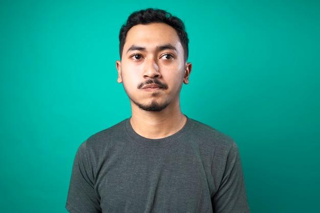 Portret van denkende en verwarde jonge man op blauwe achtergrond