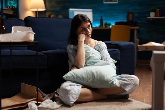 Portret van depressieve kwetsbare gestresste wanhopige vrouw die in de camera kijkt terwijl ze alleen op de bank zit
